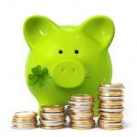 Green piggy bank with clover and coin stacks
